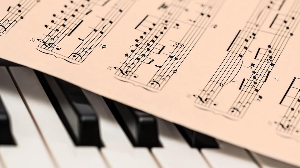 Gros plan sur des partitions de musique classique qui ont été déposées sur un clavier de piano.