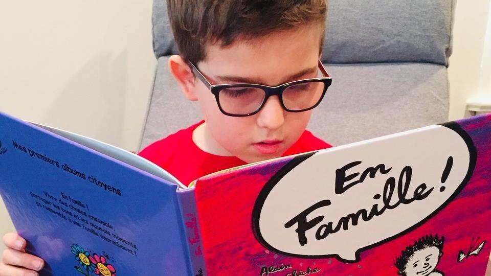 Le jeune Émile lit le livre « En famille ».