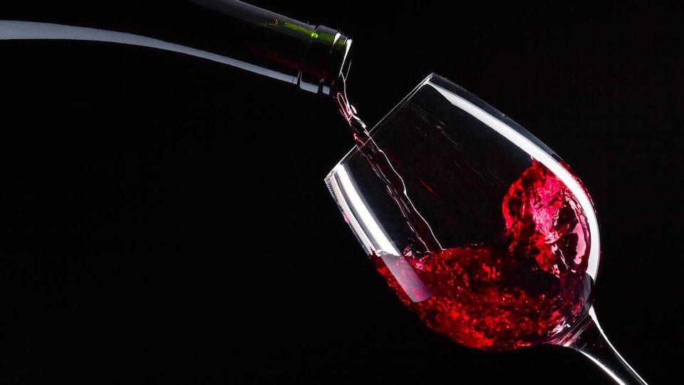 Le contenu d'une bouteille de vin rouge est versé dans un verre.
