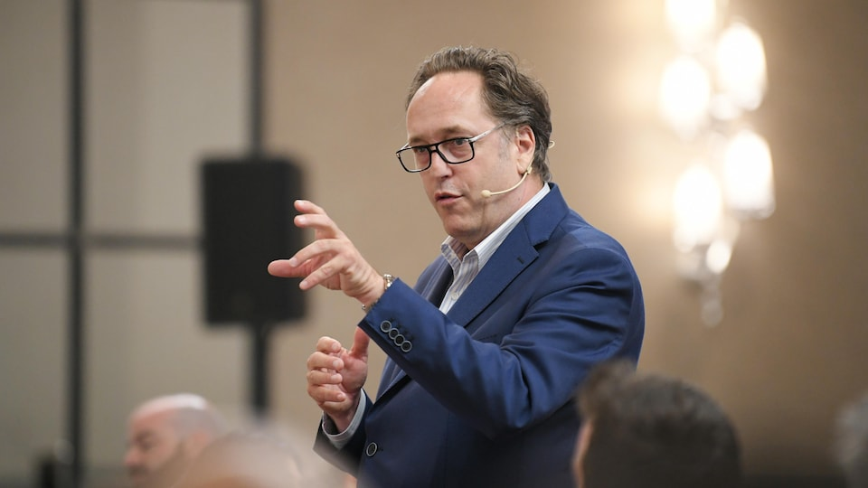René Villemure parle devant une assemblée. Il est debout et porte un costume bleu.