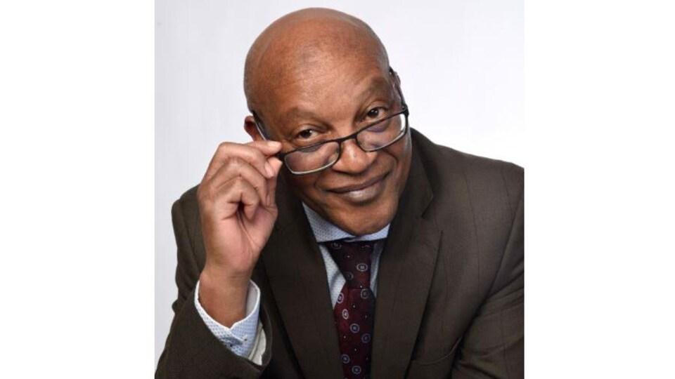 Melchior Mbonimpa sourit à la caméra en tenant la branche droite de ses lunettes.