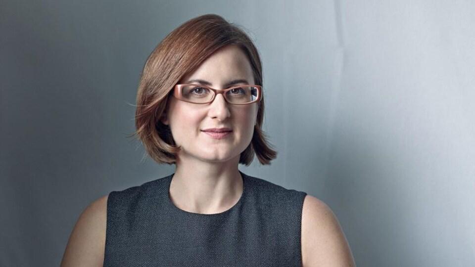 Portrait de Christine Mainville, elle porte un vêtement gris, des lunettes cerclées de brun et regarde la caméra.