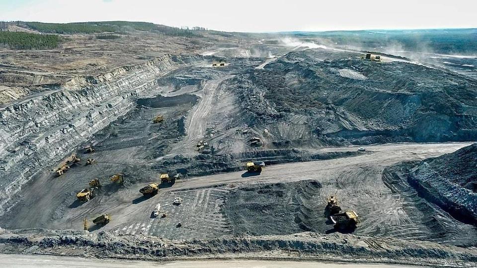 Une photo aérienne de la mine où plusieurs camions à benne et tractopelles exploitent le minerai.