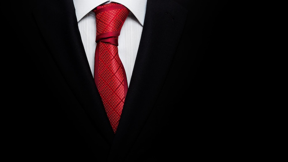 Un complet noir, une chemise blanche et une cravate rouge.