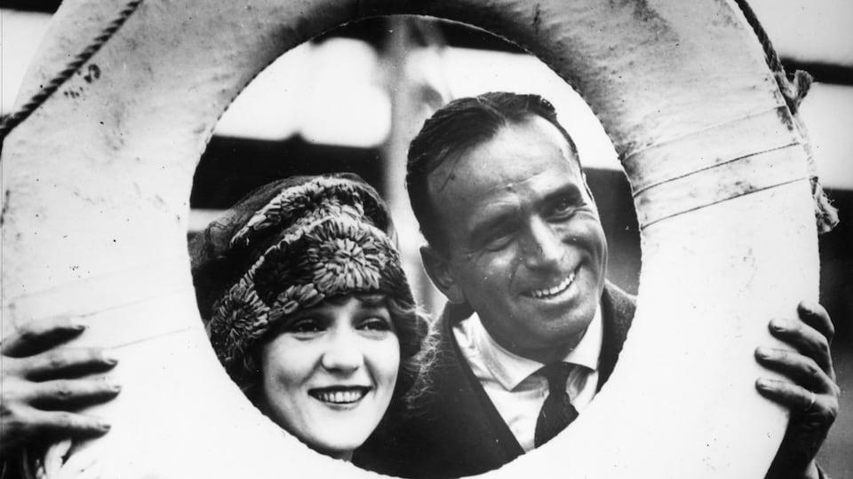 Douglas Fairbanks et Mary Pickford posent derrière une bouée de sauvetage en 1920.
