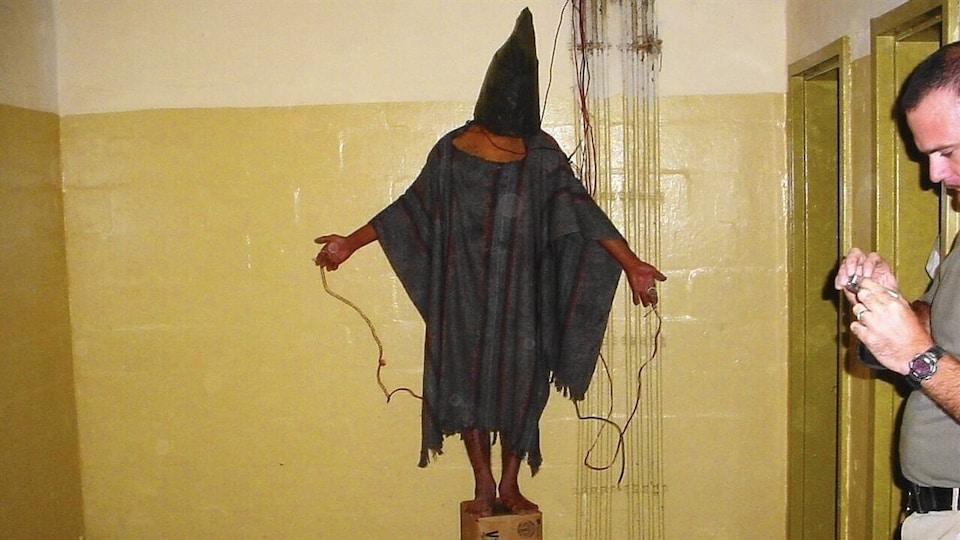Une personne est debout sur une chaise et a des fils électriques attachés aux doigts des deux mains.