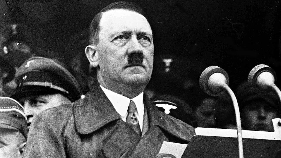 Un homme moustachu se tient devant une tribune et deux micros.