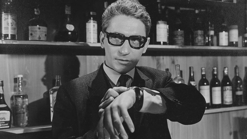 Hubert Aquin ajuste sa montre devant les étagères d'un bar dans une scène du film Faux bond (1966), de Louis-Georges Carrier.