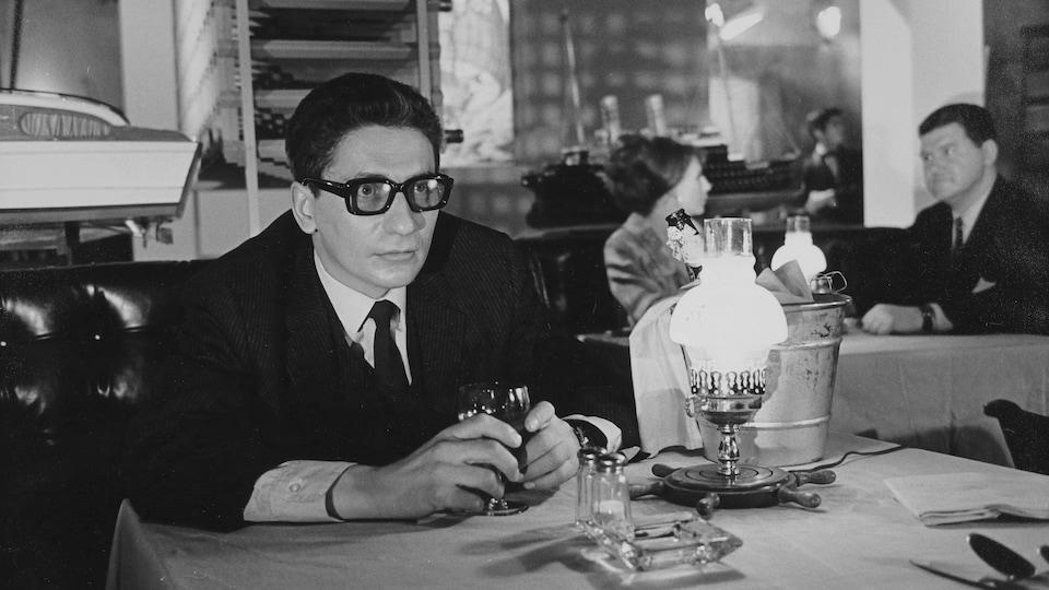 Hubert Aquin assis à une table de restaurant dans le film Faux bond (1966), de Louis-Georges Carrier.
