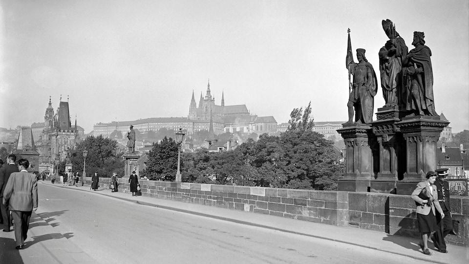 Une photo en noir et blanc de passants qui marchent sur le pont Charles à Prague, en République tchèque.