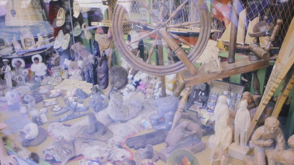 Des objets d'art traditionnel québécois exposés dans la vitrine d'un magasin.