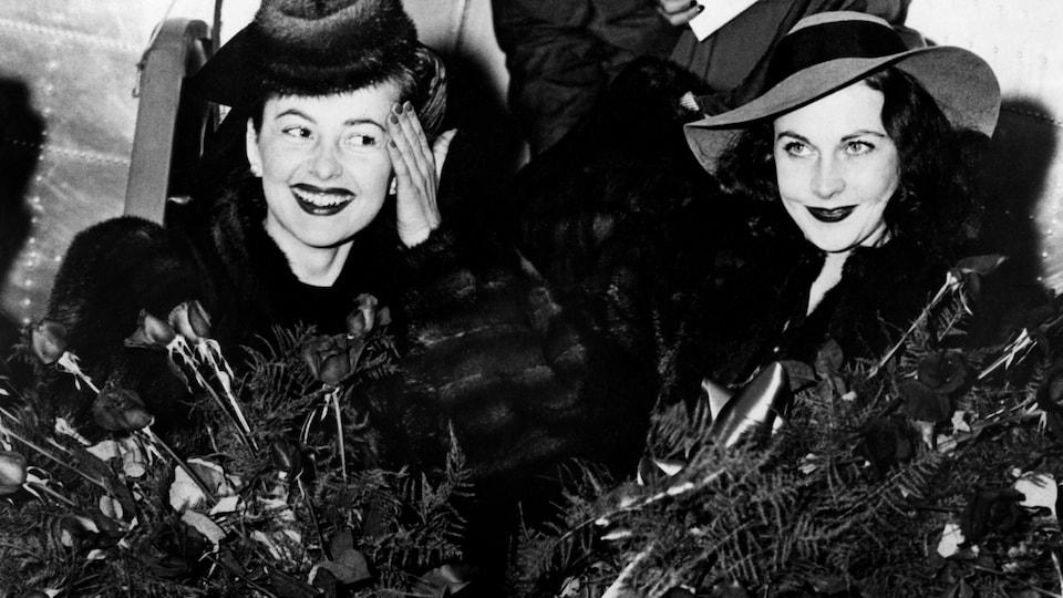 Deux femmes vêtues de manteaux de fourrure tenant des bouquets de fleurs.