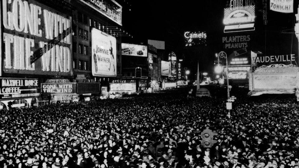 Photo en noir et blanc d'une foule dense rassemblée à Times Square.