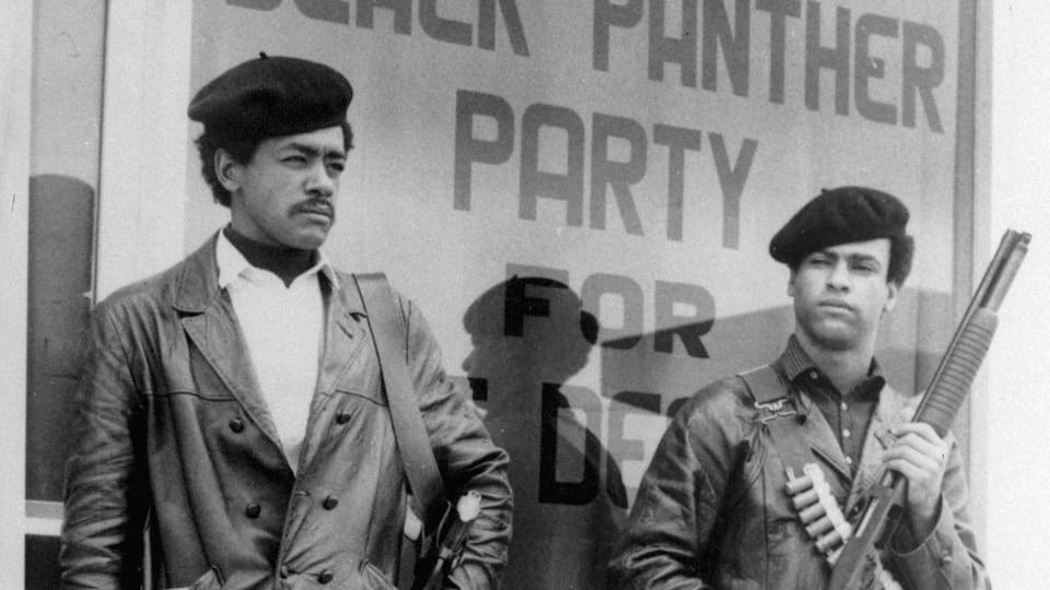 Photo en noir et blanc montrant les deux hommes armés.