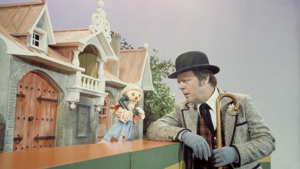 Devant sa maisonnette, Bobinette (voix de Christine Lamer) parle au téléphone tandis que Bobino (Guy Sanche), debout devant le comptoir, l'écoute.