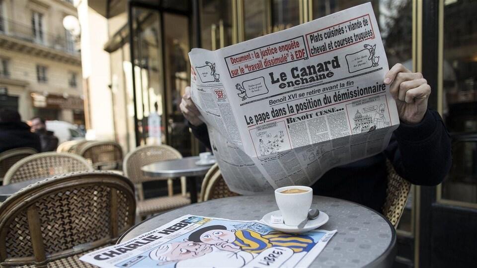 Attablé à un café français typique, un homme lit Le canard enchaîné, le visage caché par le journal grand ouvert entre ses mains.