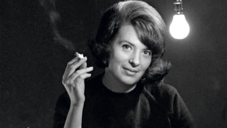 Marie Cardinal, devant une machine à écrire, sourit en tenant une cigarette.