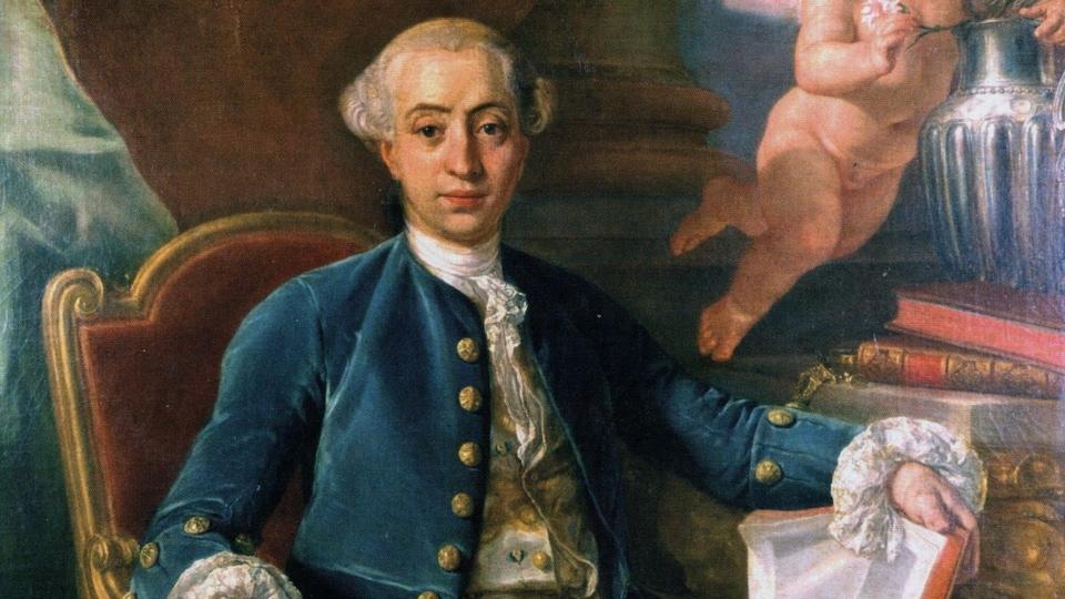 Casanova assis dans un fauteuil, livre ouvert à la main.