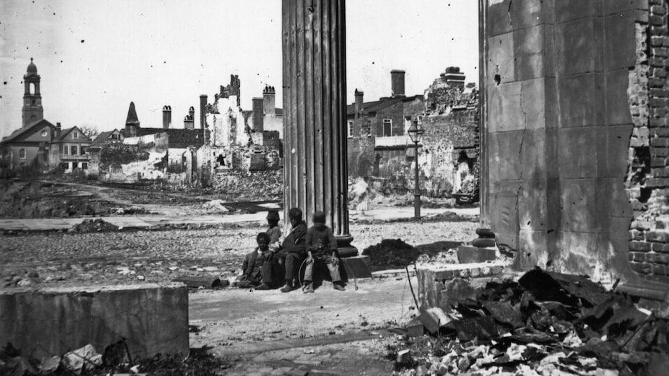 Des enfants noirs sont assis dans les ruines de la ville de Charleston, en Caroline du Sud.