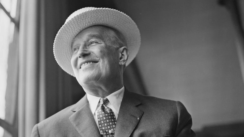 Maurice Chevalier, vêtu de son fameux canotier, regarde par une fenêtre en souriant.