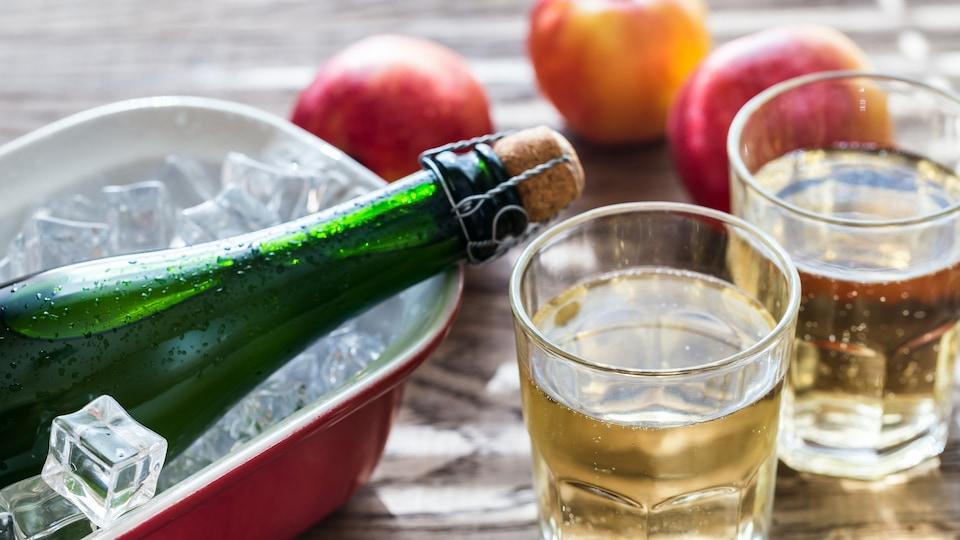 Une bouteille et deux verres de cidres sur une table en bois