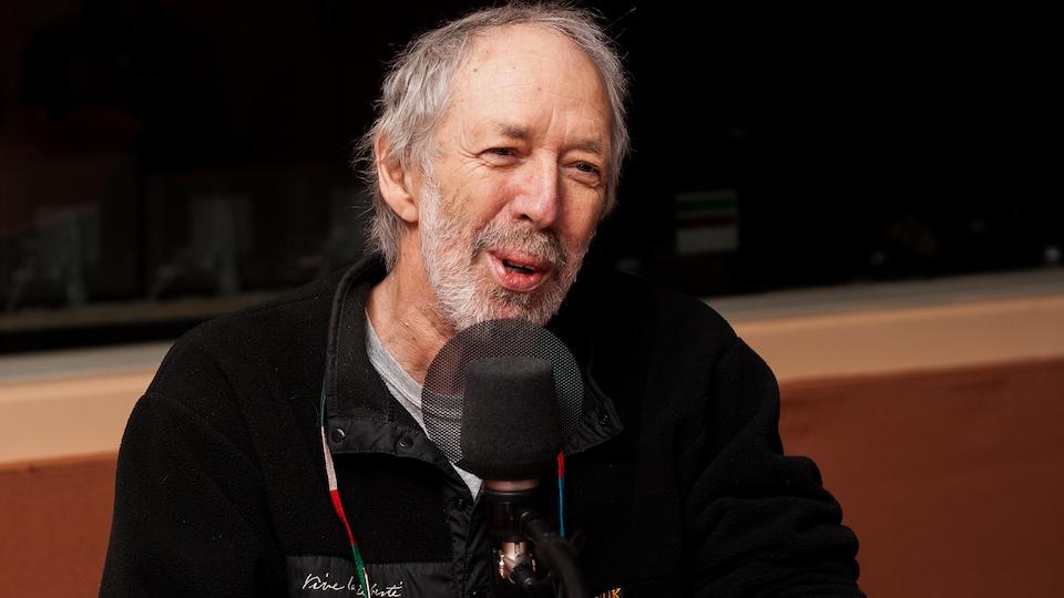 Le réalisateur offre un sourire narquois à l'animatrice Christiane Charette, en entrevue à Radio-Canada en 2009.