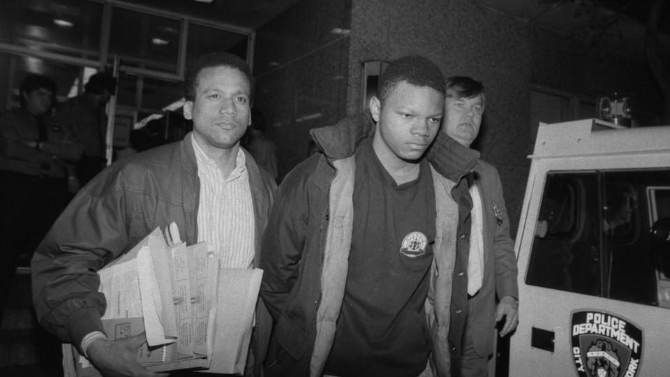 Un jeune homme menotté est escorté par deux hommes à ses côtés.