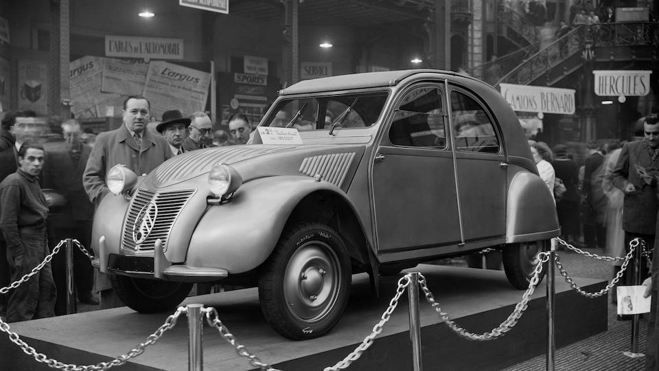 La Citroën 2 CV exposée sur un socle au Salon de l'auto de Paris de 1948.