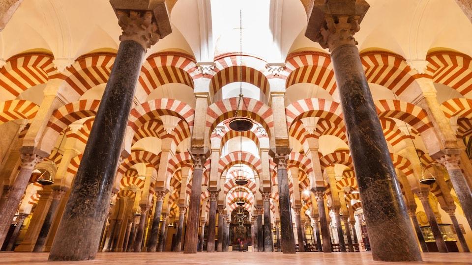 Piliers de marbre et arcades aux  couleurs vives à l'intérieur de la mosquée-cathédrale de Cordoue.