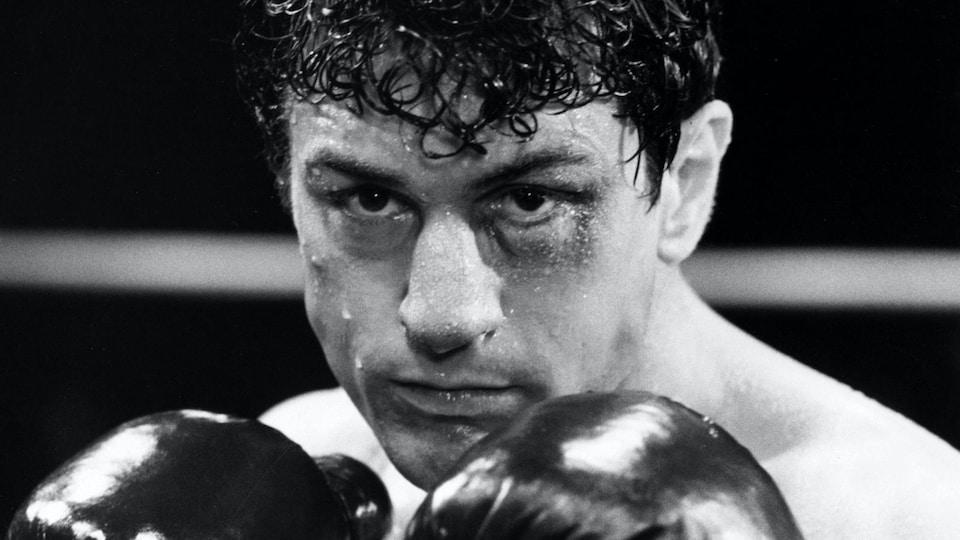 Gros plan sur Robert De Niro, en gants de boxe sur le ring, dans une image tirée du film Raging Bull, de Martin Scorsese.