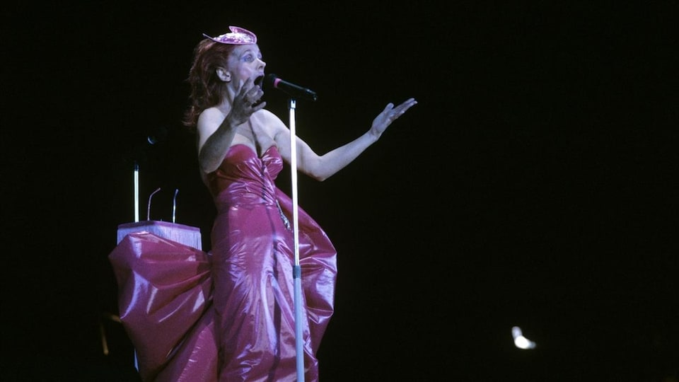 Une femme portant une robe rose chante sur scène dans un micro.