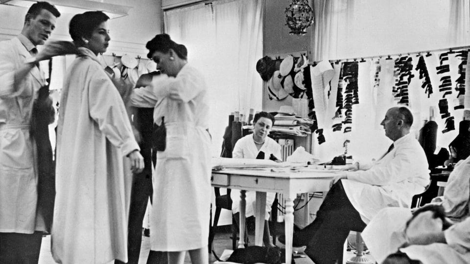 Des employés s'affairent autour du couturier Christian Dior en 1956.