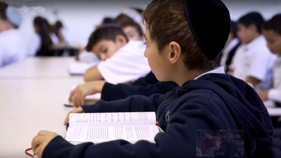 Un élève juif sépharade se tient devant un livre devant d'autres élèves en arrière plan.