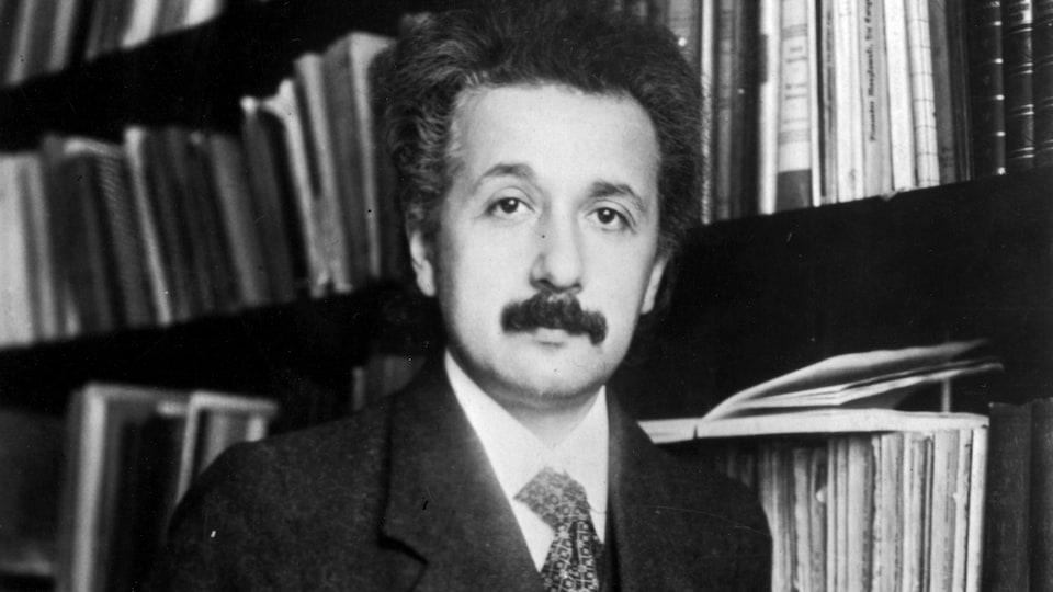 Albert Einstein devant une bibliothèque.