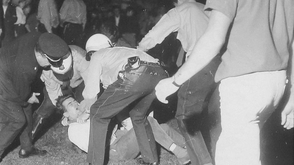 Un homme est maîtrisé par des policiers lors de la manifestation du 10 septembre 1969 à Saint-Léonard.