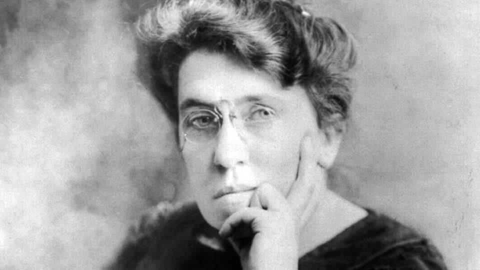 Photo en noir et blanc d'une femme avec des lunettes posant la main sur le visage.