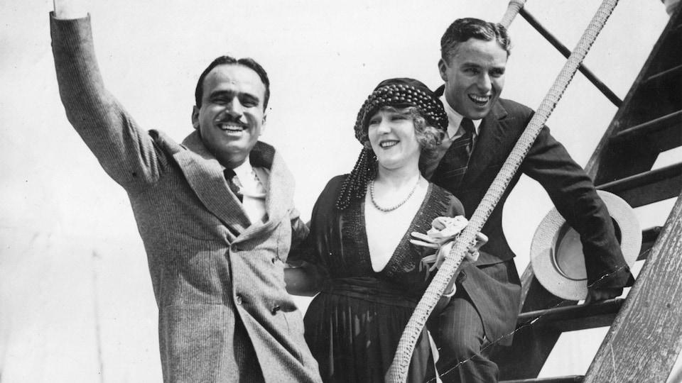 Douglas Fairbanks, Mary Pickford et Charlie Chaplin dans l'escalier d'un avion.