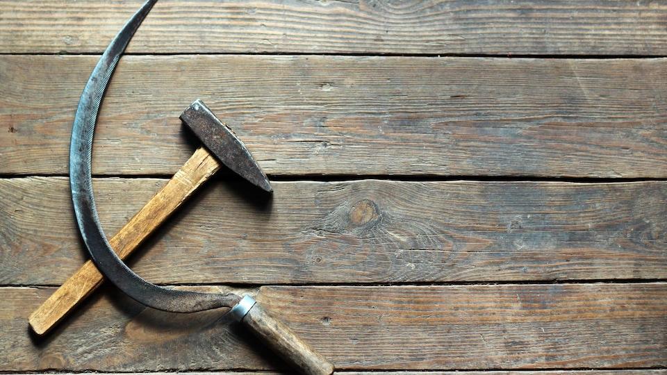 Une faucille et un marteau formant l'emblème communiste sur une table de bois.