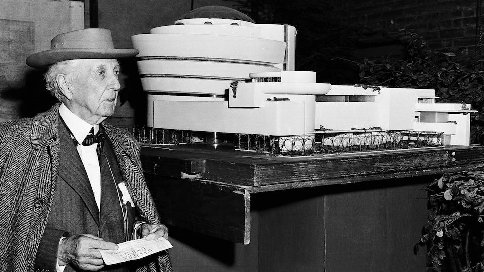 Frank Lloyd Wright se tient debout, à gauche d'une maquette du musée Guggenheim. Il porte un chapeau.