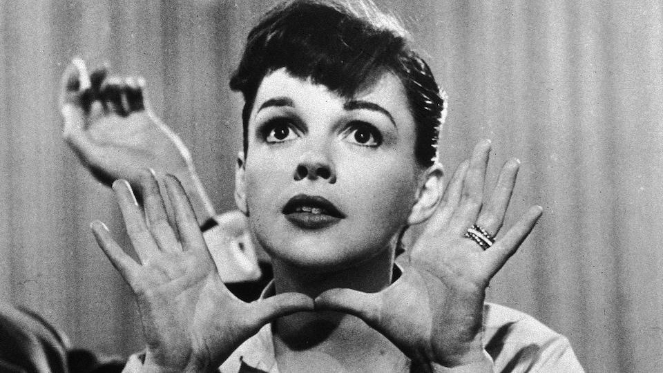Judy Garland regarde au loin, ses deux mains ouvertes entourant son visage.