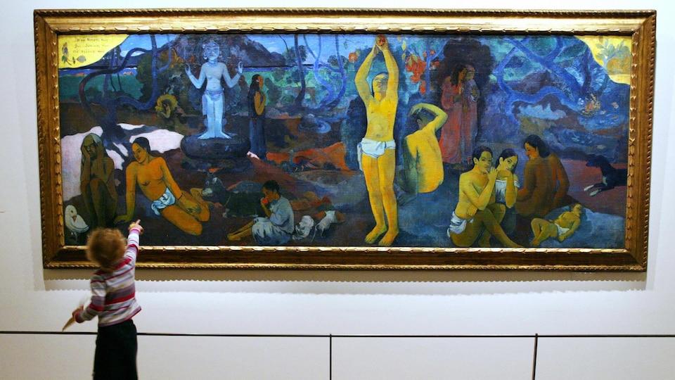 Une enfant regarde la peinture <i>D'où venons-nous? Que sommes-nous? Où allons-nous?</i> (1897-1898), de Paul Gauguin.