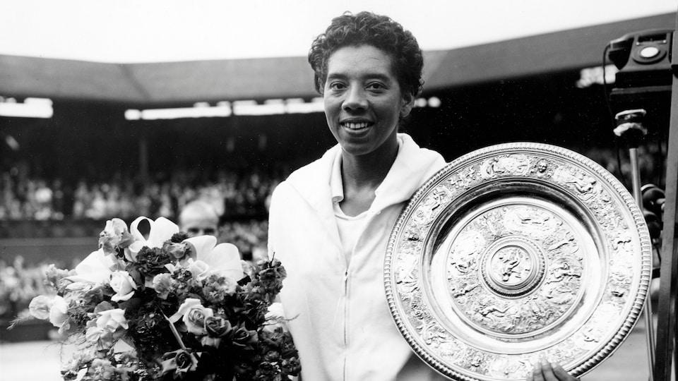 Althea Gibson tient une gerbe de fleurs et le plateau d'argent de la victoire lors du tournoi de Wimbledon 1958.