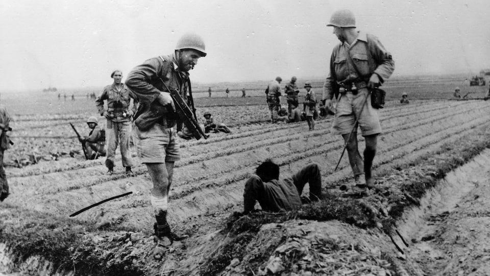 Photo en noir et blanc de soldats qui obligent un homme à sortir d'un trou dans un champ.