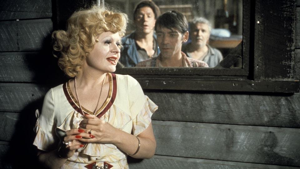 Dans une étable, la femme de Curley (Luce Guilbeault) est debout près d'une fenêtre à travers laquelle on voit Lennie (Jacques Godin), George (Hubert Loiselle) et Candy (Jean Duceppe) qui l'observent.
