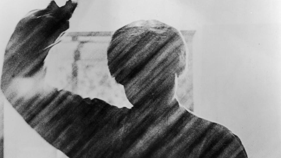 Devant le jet d'eau d'une douche, une silhouette de femme brandit un couteau.