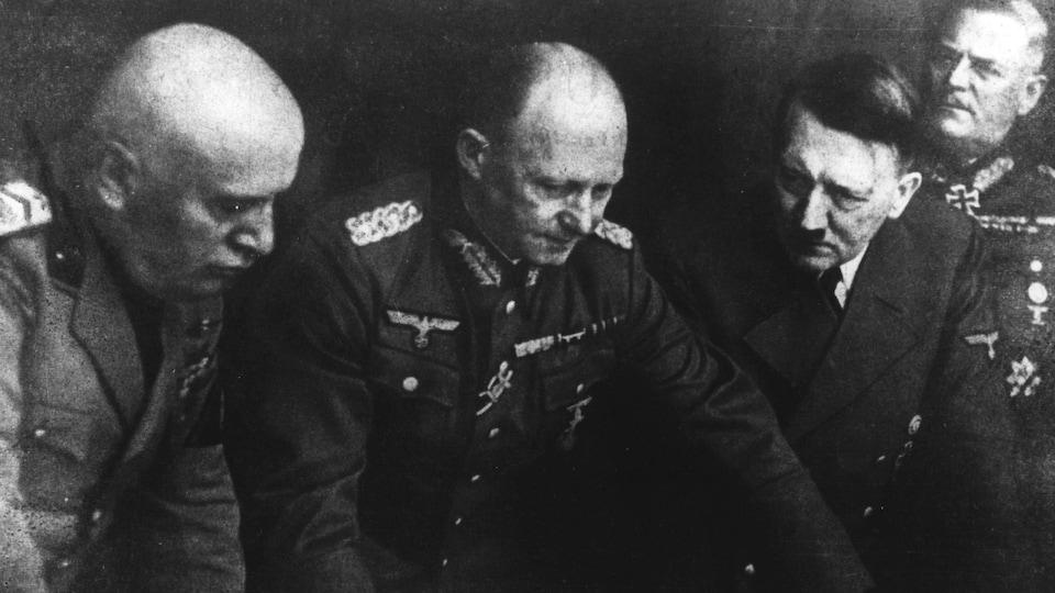 Penchés, Benito Mussolini, Adolf Hitler et les officiers allemands Alfred Jodl et Wilhelm Keitel regardent des documents.