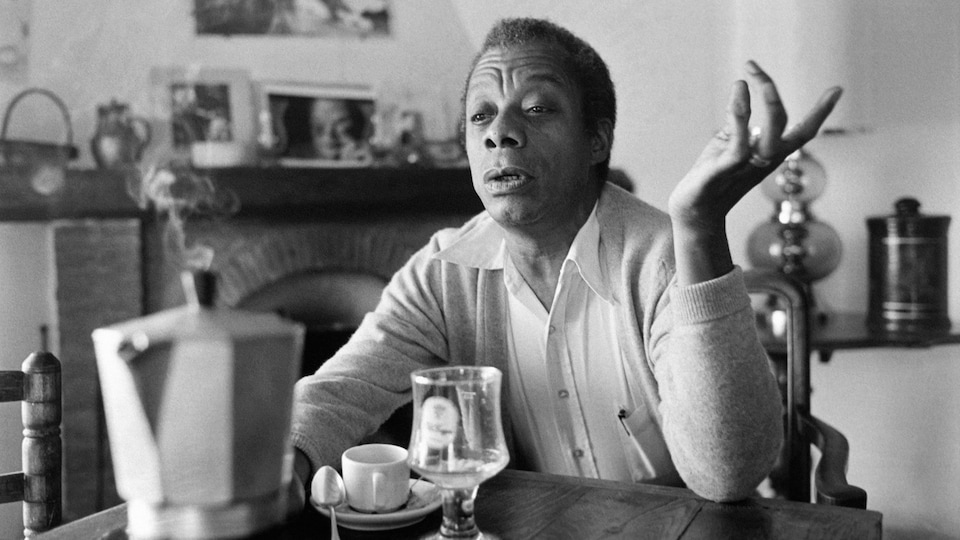 Photo en noir et blanc d'un homme assis dans une cuisine.