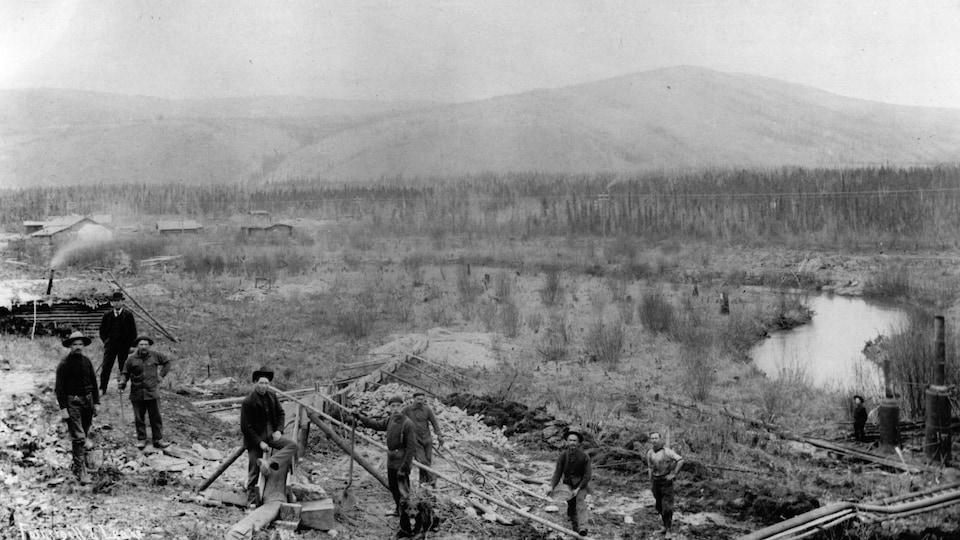 Photo en noir et blanc montrant des prospecteurs au travail durant la ruée vers l'or du Klondike, en 1898.