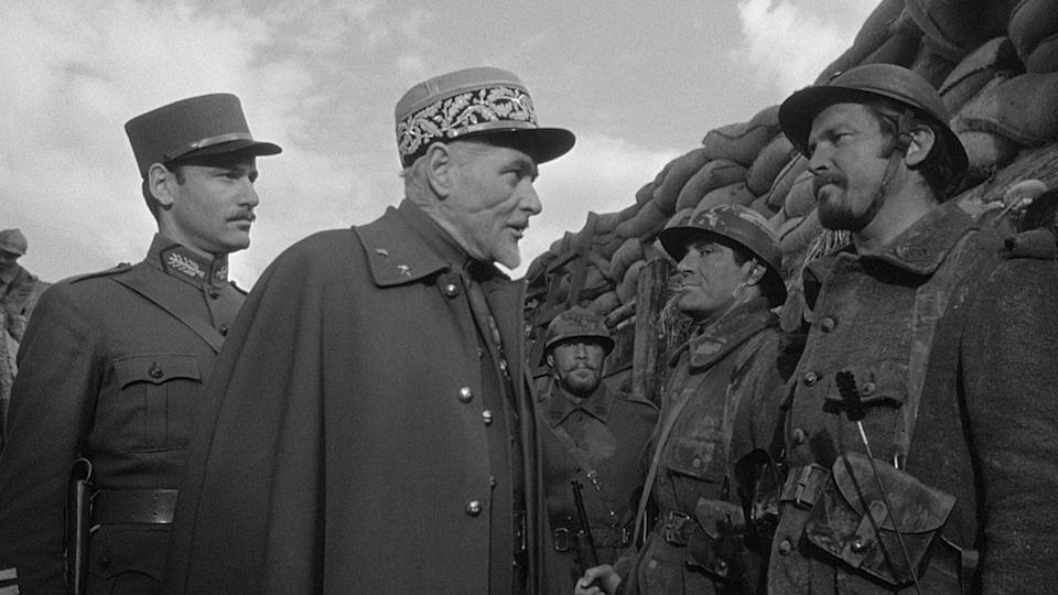 Des officiers inspectent des soldats dans une tranchée.