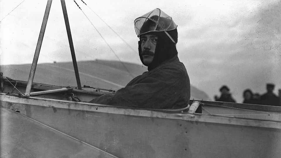 Photo de 1909 montrant Jacques de Lesseps, de profil, assis aux commandes d'un avion au sol.